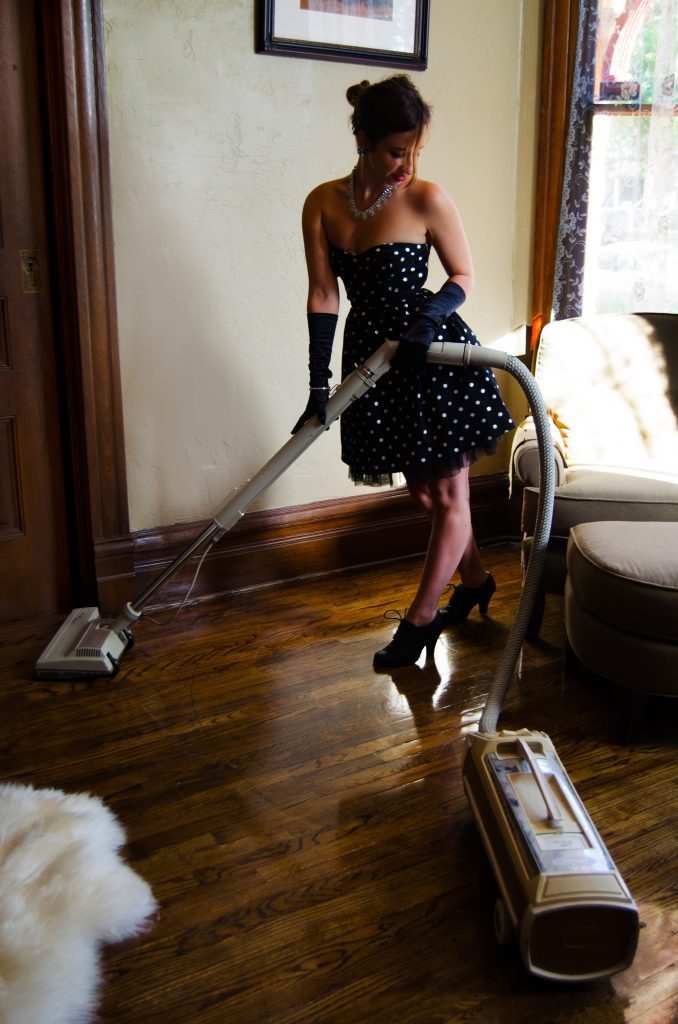 Girl vacuuming in pin up dress